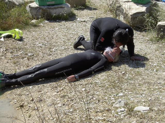 The first step for treating someone in shock is to get them to lie still on their back. It would be better to have this diver's feet elevated.